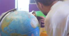 Little Blonde Girl With Long Hairs Kid is Standing at a Globe Rotating the - stock footage