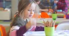Little Blonde Girl Kid Shows a Sheet of Paper Talking Sitting at The Table on Stock Footage