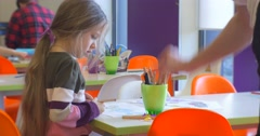 Educator's Hand Takes a Pencil From a Cup Kid Little Blonde Girl is Sitting at Stock Footage
