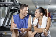 Trainer discussing a woman client's workout schedule Stock Photos