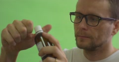Man in Glasses Patient in White T-Shirt Opens a Bottle and Drips the Medicine - stock footage