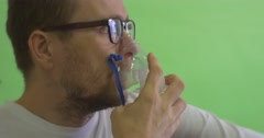 Man is Glasses Patient in White T-Shirt Keeping Nebulizer Mask at His Face - stock footage