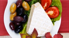 Aged camembert cheese on green salad Stock Footage