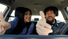 Man and woman making ok sign while driving car Stock Footage