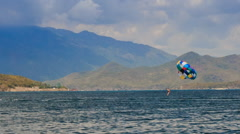 Stock Video Footage of view of parasailing over azure sea against mountains