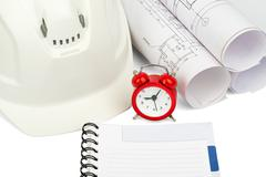 Blueprint rols and helmet with alarm clock - stock photo