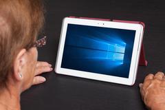HEERENVEEN, NETHERLANDS, June 6, 2015: Tablet computer with Windows 10 backgr Stock Photos