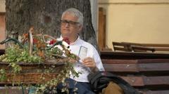 Elderly man sitting on a bench, Sighisoara Stock Footage