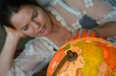 Stock Photo of Young woman search for a travel destination on a vintage globe