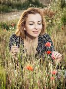Beautiful woman posing in poppy flowers field, beauty, fashion and nature - stock photo