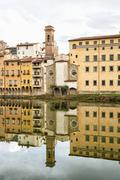 Historical buildings with bell tower mirrored in the river Arno, Florence, Tu - stock photo
