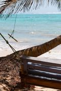 Wooden Bench Swing next to a palm tree in front of the caribbean white sand - stock photo