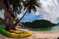 Yellow kayak laying on the sand beach with palm tree - stock photo
