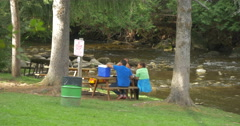 People eating at a wooden table near the river at Belfountain, Canada Stock Footage