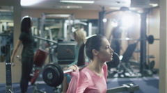 Attractive fit sporty girl is exercising squats with barbell in the gym - stock footage