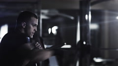Professional male boxer is training punches and kicks in dark gym - stock footage