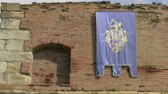 Blue flag on a brci wall at Fagaras fortress Stock Footage