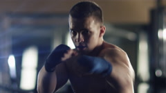 Professional male boxer is training punches and kicks in the gym - stock footage