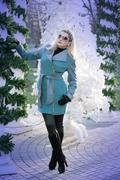 Stock Photo of the beautiful woman in a turquoise coat at the columns braided by fir-tree br