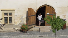Woman exiting a door and tripping in Fagaras fortress Stock Footage