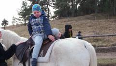 Children's rehabilitation with the help of horses. Boy doing exercises Stock Footage