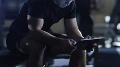 Handsome fit sporty man is using a tablet computer in the gym - stock footage