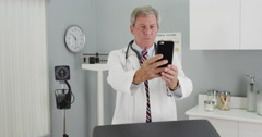 Senior doctor using smartphone to take a selfie Stock Footage