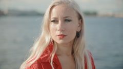 Woman in red jacket sits near the river Stock Footage