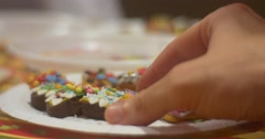 Stock Video Footage of Young Woman's Hand Takes a Cookie Turns It Checks the Decoration Crumbs Strew