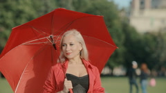 Beautiful blonde walks in the park with a red umbrella Stock Footage