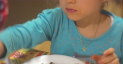 Stock Video Footage of Little Blonde Girl in Blue Blouse is Sitting And Putting a Decorative Crumbs to