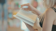 Girl flips through a book in a bookstore Stock Footage