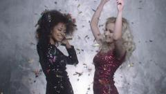 Two sexy girls dancing among colorful confetti in studio. Stock Footage