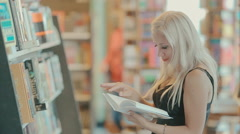 Young woman in a bookshop Stock Footage