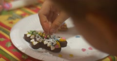 Stock Video Footage of Childish Hands Are Decorating a Biscuit Man Cookie with Colorful Crumbs Cookie