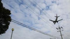 Airplane flying overhead against electric pole and cloudy sunny sky Stock Footage