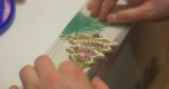Kid's Hands Are Packing a Fir Tree-Shaped Christmas Cookie into a Polyethylene Stock Footage