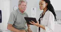 Woman doctor talking with senior patient in the office Stock Footage