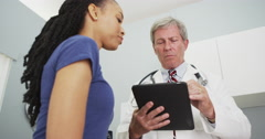 Senior doctor looking over African woman's medical history - stock footage