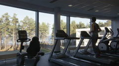 Handsome fit sporty man is running on a treadmill in the gym - stock footage