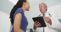 Senior doctor advising young black woman - stock footage