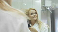 Attractive blond girl is drying her hair with a hairdryer in a bath - stock footage