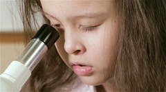 Young girl scientist looking into microscope and around d - stock footage