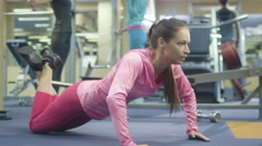 Attractive fit sporty girl is exercising pushups in the gym Stock Footage