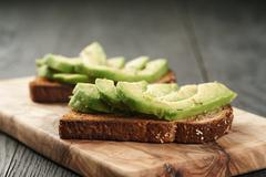 Toasted rye bread with sliced avocado and herbs Stock Photos