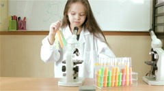 Child scientist putting test tubes away and checking microscope slider in MS. Stock Footage