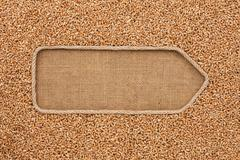 Pointer made from rope with grain wheat  lying on sackcloth - stock photo