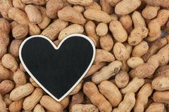 Heart pointer, the price tag lies on peanut - stock photo