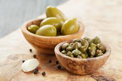 green huge olives and capers on wood table - stock photo