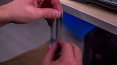 Cutting a silver tape with a razorblade Stock Footage